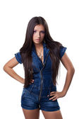 Brunette young woman in jeans overalls — Stock Photo