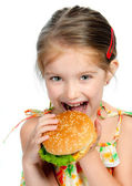 Little girl eating a sandwich isolated — Stock Photo