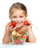 Little cute girl holding a strawberry — Stock Photo