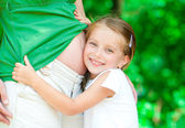 Girl hugging mother's belly — Foto de Stock