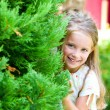 Girl looks out behind a tree — Stock Photo