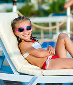 Little girl lies on a chaise lounge — Stock Photo