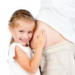 Little girl with stomach of pregnant mother — Stock Photo #12307347