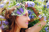 Beautiful woman with butterfly in the garden — Stock Photo