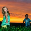 Group of happy children playing on meadow, sunset, summertime — Stock Photo
