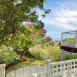 Back yard white fence and deck with water view. - Stock Photo