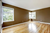 Empty room with brown walls and hardwood floor. — 图库照片