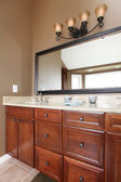 Close up luxury wood bathroom cabinets and mirror. — Stock Photo