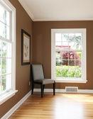 Canto de sala de estar com uma cadeira e duas janelas. — Foto Stock