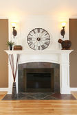 Luxury home white fireplace with stone and clock. — Stock Photo
