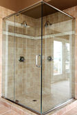 Modern new glass walk in shower with beige tiles. — Stock Photo