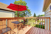 Deck with red umbrella with warm wood. — Stock Photo