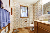 Old brown bathroom with wallpaper and blue towels. — Photo