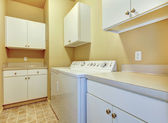 Laundry room with white cabinets and yellow walls. — Stock Photo