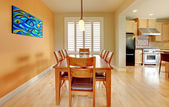Orange dining room with hardwood floor and kitchen. — Foto de Stock
