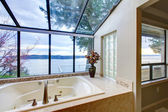 Large tub with glass wall with water view. — Stock Photo