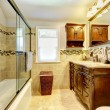Nice bathroom with natural stone tiles and wood cabinet. - Stock Photo