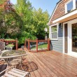 House exterior with large open deck with outdoor furniture. - Stock Photo