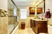 Nice bathroom with natural stone tiles and wood cabinet. — Stock Photo
