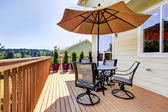 Deck with table, chairs and umbrella. — Stock Photo