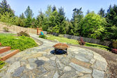 Fenced backyard with stone and fire pit with trees. — Stock Photo
