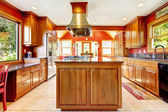 Large red luxury kitchen with wood and tiles. — Stok fotoğraf