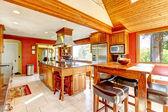 Grande cozinha com paredes vermelhas e tecto abobadado madeira. — Foto Stock
