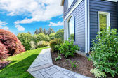 Modrý dům strana s chodníkem a zelená krajina. — Stock fotografie