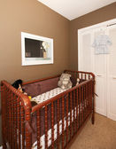 Cherry wood baby crib in nursery interior. — Stock Photo