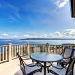Stock Photo: Luxury home balcony deck with water view and table.