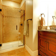 Bathroom with wood cabinet and tile shower. — Stock Photo