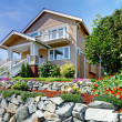 Two story beige nice house on the rocky hill with flowers. — Stock Photo #12075529