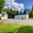 Stock Photo: Small grey house with workshop and large parking lot.