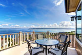 Luxury home balcony deck with water view and table. — Stock Photo