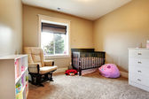 Nursing room for baby girl with brown wood crib. — Stock Photo