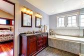 Lavendar lindo baño con bañera y gabinete con dos lavabos de madera. — Foto de Stock