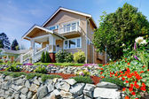 Two story beige nice house on the rocky hill with flowers. — Stock Photo