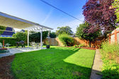 Backyard with fence and house covered deck. — Stock Photo