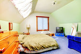 Attic large bright simple bedroom with green walls. — Photo
