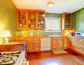 Green kitchen with wood cabinets and hardwood floor. — Photo