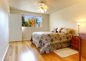 Simple bedroom with hardwood floor and fall window view. — Foto de Stock