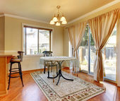 Dining room area with doors and window and simple round table. — Stock Photo