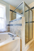 Shower with beige and blue tiles and white tub. — Stock Photo
