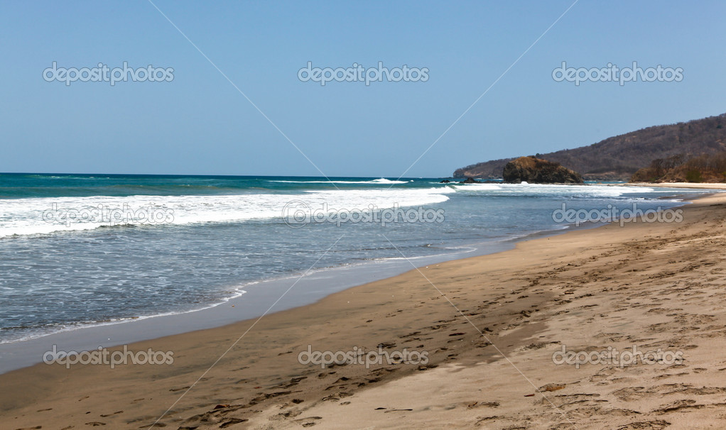 Clear blue water of the Pacific Ocean washes up on the pristine sand of Costa Rica on a clear blue sky day. — Stock Photo #10740557