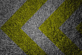 Yellow and black warning sign on grass texture — Stock Photo
