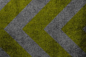Yellow and black warning sign on fabric texture — ストック写真