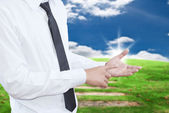 Businessman putting touch screen on blue sky field. — Stock Photo