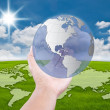 Hand pushing globe on the blue sky field — Stock Photo #11554828