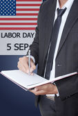 Asian businessman writing on notebook on labor day. — Stock Photo