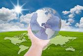 Main en poussant le globe sur le champ de ciel bleu — Photo